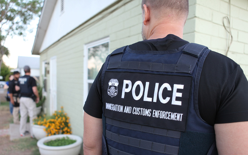 An ICE officer outside a house